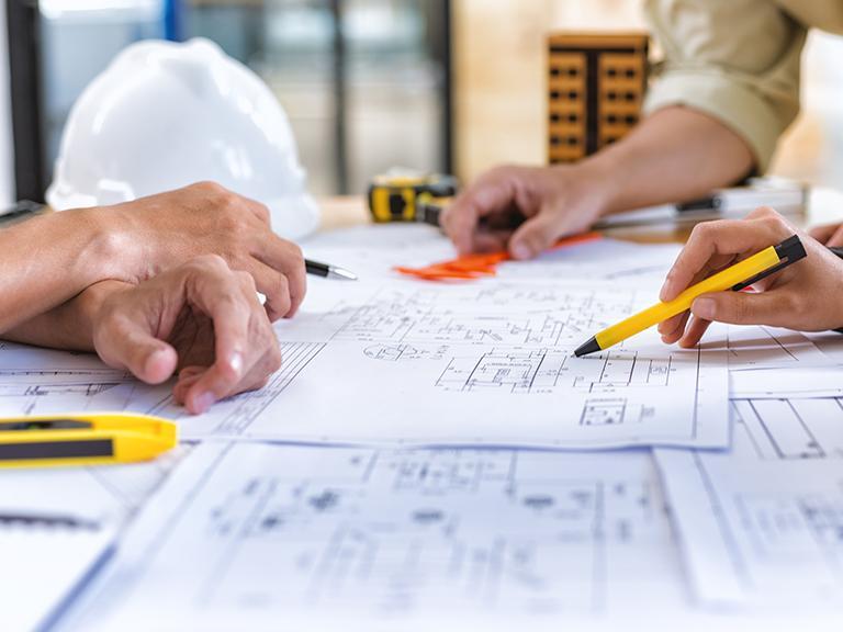 Kilka osób analizująca plany zrzutowe budynku